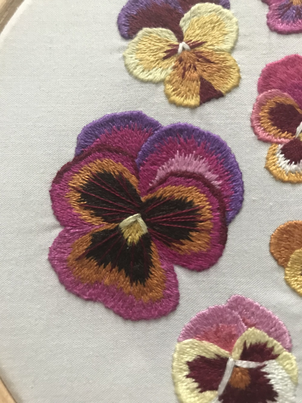 Pansy embroidery hoop art created through thread painting.jpg