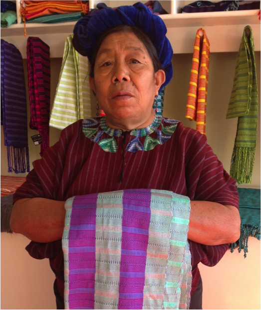 Ana Cumes Santos Simón - Ana is a weaving artisan for Manos Cruceñas Artisan Store (the retail store for Amigos de Santa Cruz) who makes beautiful scarves for ixöq using a belt-loom. She is 65 year's old and lives with her husband and seven children. Ana also makes the traditional Santa Cruz red blouses (Ana is wearing one in the photo) for sale in the village of Santa Cruz. Working as a weaver allows Ana to cover her expenses at home as she and her husband have limited work opportunities now they are getting older. Ana is very grateful for the opportunity to work with Manos Cruceñas over the past 5 years and most recently for ixöq and looks forward to continuing to weave beautiful products to support her family.