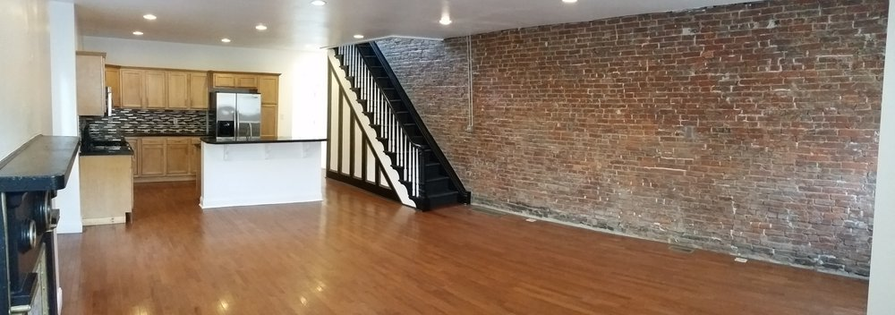 Exposed brick in this industrial spacious living area is the feature in this luxury rental apartment by Steeltown Properties in Pittsburgh, Pennsylvania