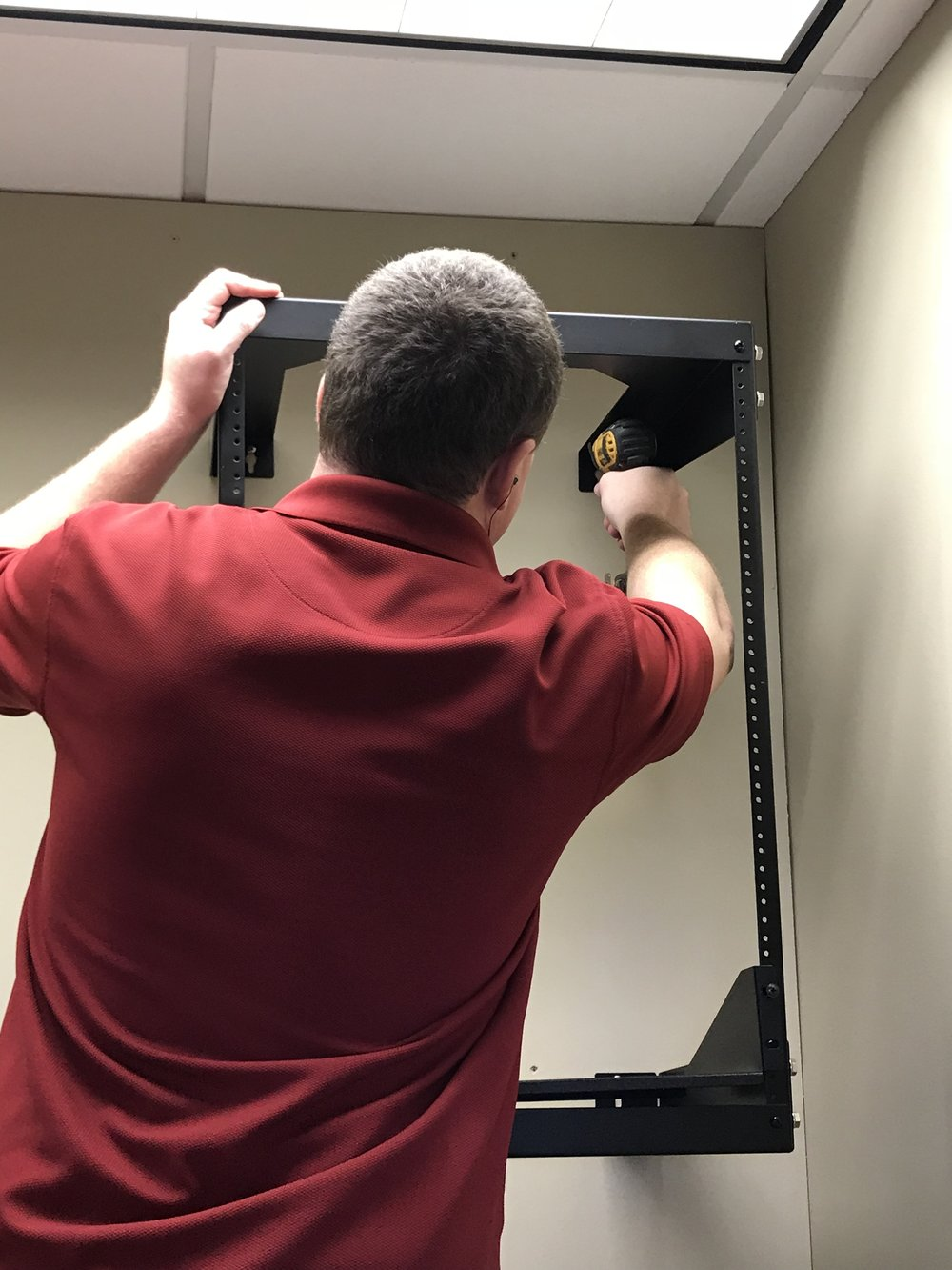 Steven installing a new telecom rack after a customer recently moved offices from North East Columbia to Downtown Columbia.