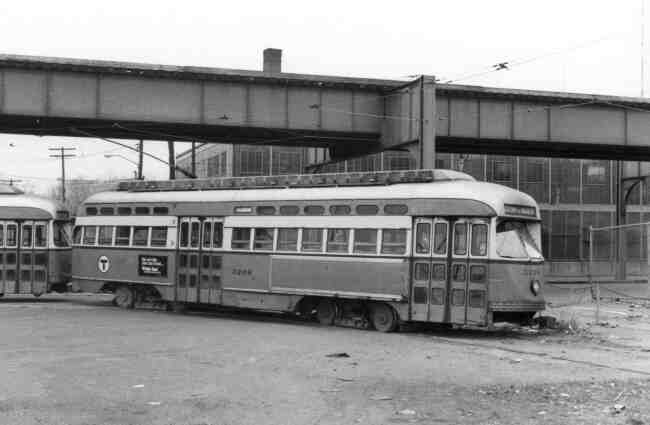 Trolley # 3206 makes its way into the Arborway yard on Washington Street in this late 1960s photo. The towering elevated structure hovers over the Kinney Vacuum building in the background.