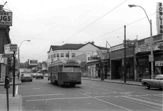 Centre & Burroughs Streets are the location for this 1960s photo showing trolley # 3043 on its journey to the Arborway. The local merchants were Boston Five Cent Savings Bank, Yumont Paint & Supply, Publix Market, F.W.Woolworth, and Rogers Drug Store.