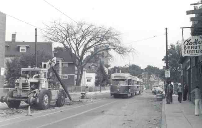 Trolley # 3047 travels cautiously towards construction work being done on South Street near Bardwell Street in this 1976 photo. The Cla-Mar Beauty Culture shop can be seen along with the sidewalk supervisors observing all of the activity.