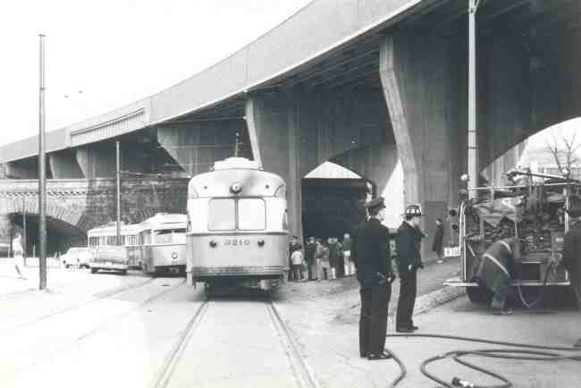 Trolley #3210 is shown in this 1967 photo after an electrical fire forced the evacuation of its passengers. The Arborway overpass is in the background.