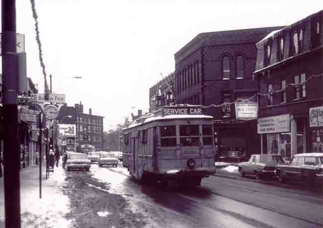 "In this 1870 view of Centre Street, a 1940s-era trolley, in use as a maintenance vehicle, passes Boston Five Bank on the left and Burroughs Street on the right. Note the ""Ask Mr. Fowler"" sign (the business is currently in another location on Centre St.). Photographs in this collection are courtesy of Frank Norton and Joe Testagrose."