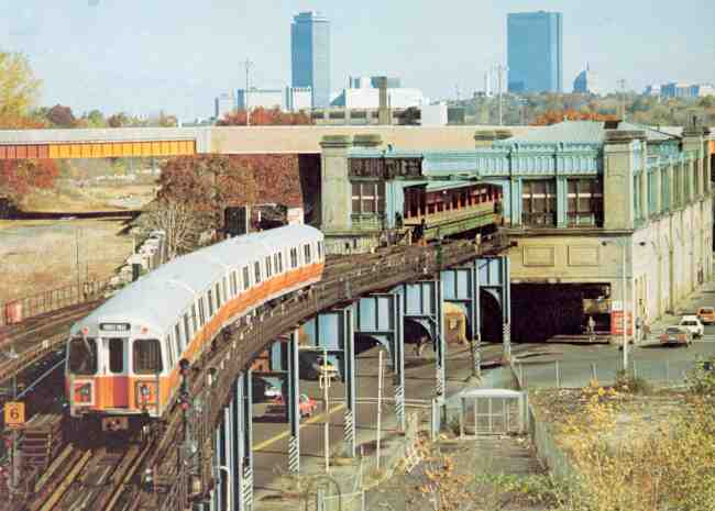 The Orange Line MBTA train reaches the end of the line at Forest Hills in this 1980s photo. The Arborway overpass can be seen along with the distant views of the Prudential and John Hancock buildings.