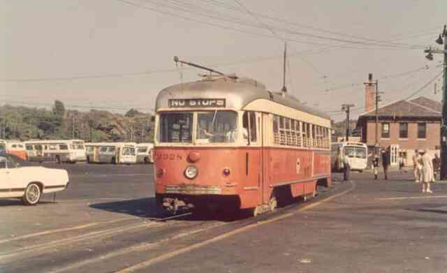 Trolley # 3328 waits for its next trip at the Arborway yard in this 1968 photo. Idle buses can be seen along with passenger waiting to board near the MBTA business office.
