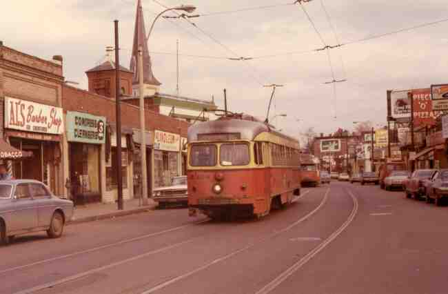 Trolley # 3328 travels down Centre Street at Seaverns Ave. on the way to the Arborway in this 1971 photo. Al's Barber Shop, Congress Cleaners, Jamaica Fruit Center, and Piece O' Pizza were all thriving businesses at the time.