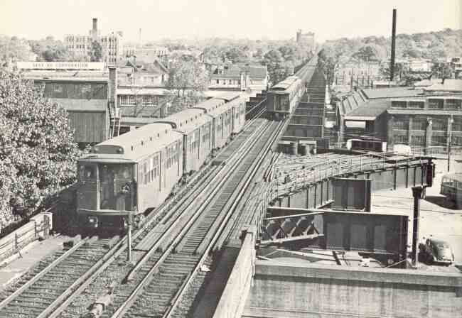 Trains traveling on Washington Street in 1953 can be seen passing the Arborway yard on the right. The Gulf Corporation building and the Boston Gas Company building can be seen to the left. In the far distance is the original Franklin Brewing Co. building.