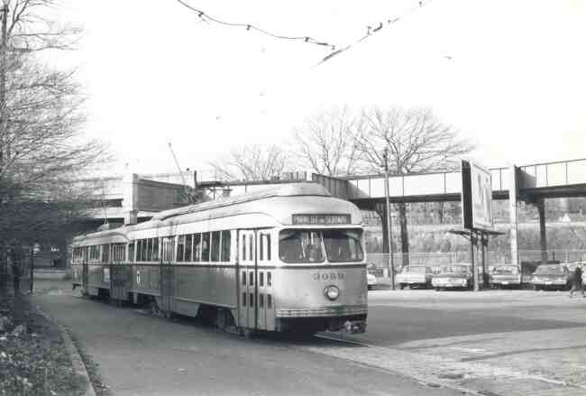 Trolley # 3059 arrives back at the Arborway yard after a trip from Park Street in this 1967 photo. The MBTA employee vehicles can be seen in the background along with the overhead train tracks on Washington Street.
