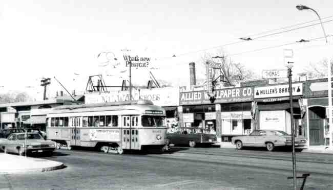 Trolley # 3065 is traveling on Centre Street at Thomas Street in this 1970 photo. The  businesses in view are Allied Wallpaper, Mullen's Bakery, Nu Way Shoes, and the Brigham's Ice Cream Shop.