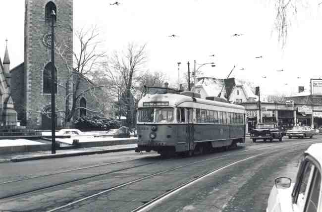 Trolley # 3328 is heading towards the Arborway on a quiet ride down South Street at the Monument in this 1965 photo. The Jamaica Drug Store at the corner of Eliot Street can be seen along with the Jamaica Driving School and Monument Fruit.