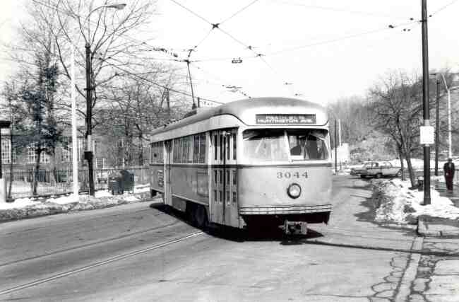Trolley # 3044 is turning from South Huntington Avenue towards the Heath Street Loop in this 1967 photo. The Longwood Hospital's wrought iron fence can be seen to the left of the trolley.