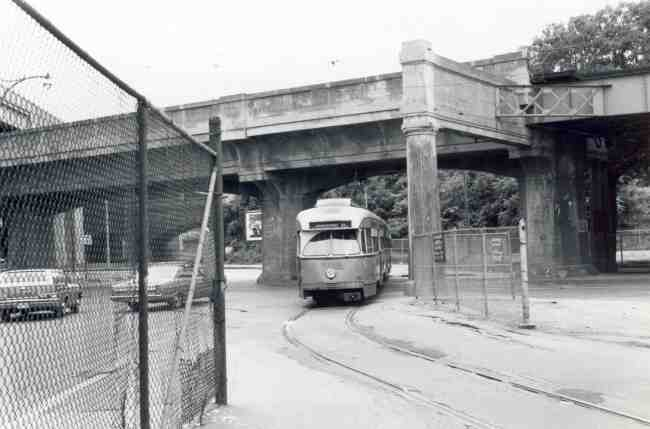 This 1968 photo shows a trolley returning to the Arborway yard while passing under the train structure on Washington Street.