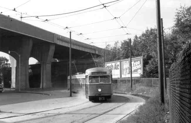 Trolley # 3034 winds its way towards the Forest Hills rotary in this 1960s photo. The Arborway overpass towers over the landscape.