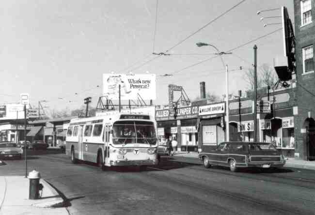 An MBTA bus travels down Centre Street towards Eliot Street in this 1970 photo. The Allied Wallpaper Co. and Mullen's Bakery are directly across from Thomas Street.