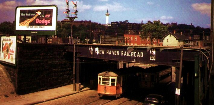 This 1947 photograph shows a trolley passing in each direction on Centre St. under the railroad bridge at Jackson Square. The standpipe on Fort Hill can be seen in the background.