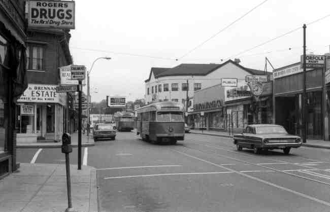 Two trolleys approach Centre & Burroughs Streets in this 1969 photo. Rogers Drugs, O'Leary & Brennan Real Estate, Yumont Hardware, Publix Market, Boston Five Cents Savings Bank, and F. W. Woolworth were a few of the businesses at the time.