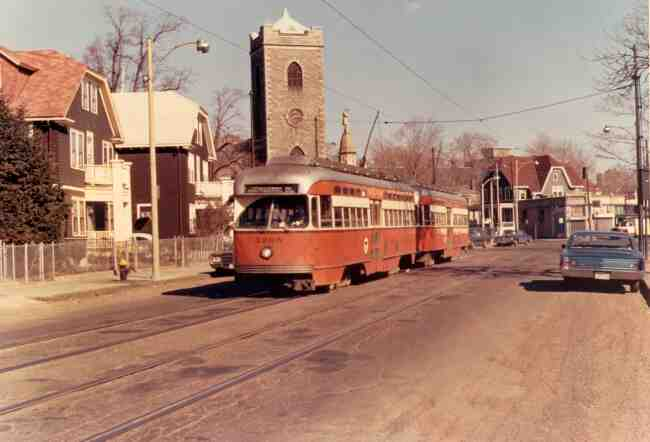 The Monument and First Church can be seen towering over trolley # 3205 as it travels on South Street near Bardwell Street in this 1971 photo. The Jamaica Drug Store can be seen in the distance at Eliot & Centre Streets.