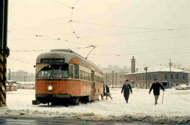 Trolley # 3220 seems to be waiting for some assistance from the MBTA Starter (in uniform) and his assistant (with the shovel) after a snow storm in this 1970 photo taken at the Arborway yard.