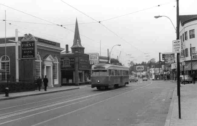 Two men pass the First National Bank of Boston while walking on Centre Street at Seaverns Ave. in this 1960's photo. The trolley is heading towards the Arborway. The First Baptist Church steeple can be seen along with the Jamaica Plain Co Operative Bank, Hailer's Drug Store, Hanlon's Women Shoe Store, and Piece O' Pizza.