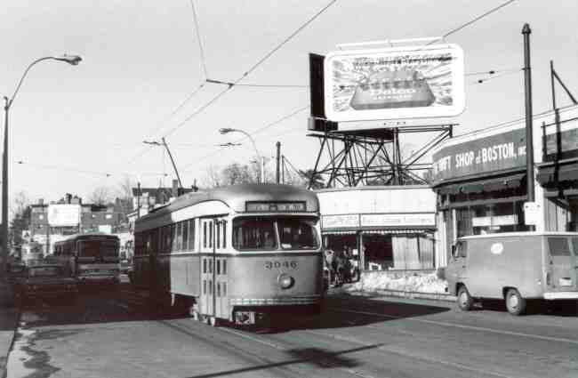 Trolley # 3046 winds its way down Centre Street in this 1969 photo. The Thrift Shop of Boston along with Centre Seafood can be seen to the right. The Donnelly advertising sign is displaying a Delco car battery ad.