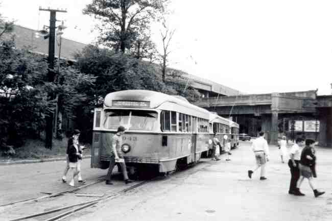 Passengers are shown making their way across the tracks in front of trolley # 3043 on its return trip from Park Street in this 1969 photo taken at the Arborway station.