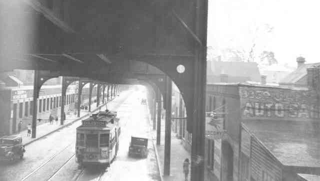 Trolley # 6392 travels down Washington Street past Green Street on its way to the Arborway in this 1938 photo. At the rear left of the trolley can be seen a boy hitching a ride on the trolley connecter. Tripp Metallic Packing is the building on the left. Socony auto repair is on the right.