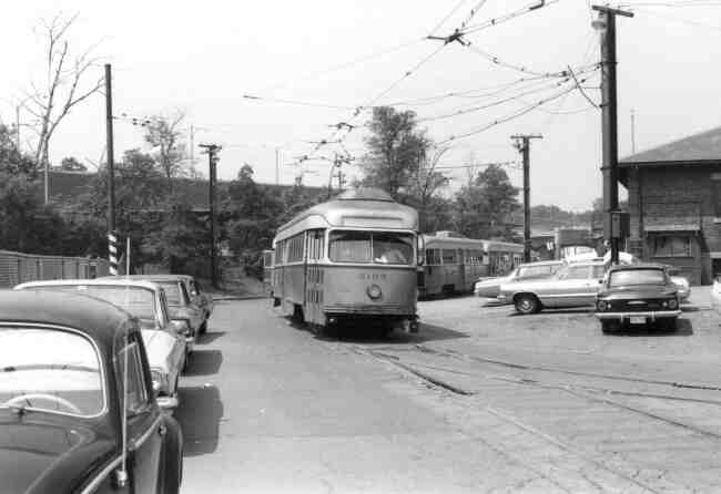 Trolley # 3103 winds its way around the rear of the Arborway yard in this 1960s photo. The vintage cars can be seen along with the view of the Arborway overpass.