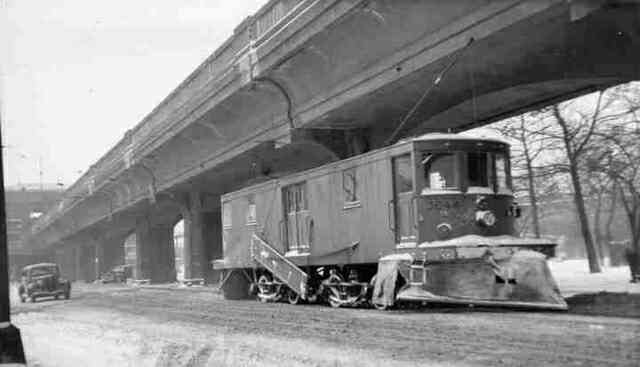 Boston Elevated snow plow # 3244 clears the tracks on Washington Street at the Arborway in this 1938 photo. Automobiles can be seen at the Forest Hills rotary.