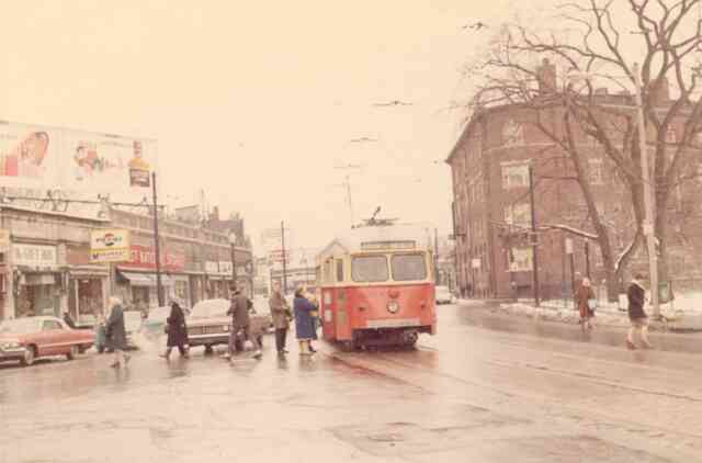 Passengers can be seen boarding trolley # 3322 on Centre Street near the Monument on this snowy day in 1967. Some of the  businesses were the local First National Grocery Store, Monument Luncheonette, The Gift Box, The Telephone business office, and the Atlantic gas station on the corner of Thomas Street.