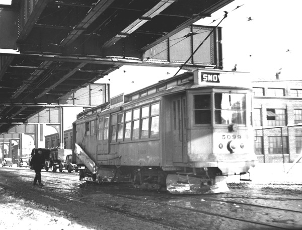 A car specially equipped to plow snow travels down Washington Street in December 1939. Now 96 years old, there are still two of these cars in service as of 2003! One is stored in Mattapan and another one at Riverside. These cars are nearly as heavy as modern Light Rail Vehicles so make great snow plows.