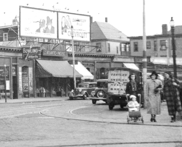 "Enlargement. In this 1938 Jamaica Plain view, car 5338 travels down Centre Street. A tiny Atlantic & Pacific (A&P) grocery store can be seen with a large awning below the billboard. To the right, just to the left of the two women walking with a baby stroller, sits a truck parked at the curb with a sign, ""Gentles Swedish Health Bread"", afixed to the rear."