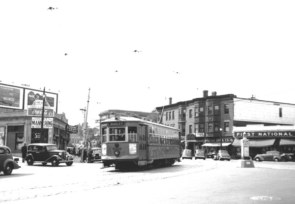 Car 5712 rounds the bend at Brigham Circle bound for Dudley Square. To the right of the car can be seen Kline Drug, Circle Restaurant, and the First National grocery store.
