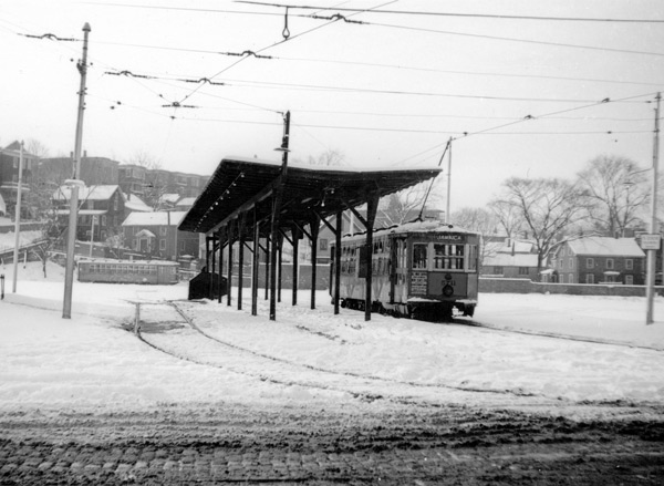 Car 5711 has taken on passengers at the Jamaica Station (Loop), where the old carhouse had been located, and prepares to begin its return trip. This photograph was taken in December 1939. Housing on Woodman Street, Ballard Way, and Jamaica Street can be seen in the background. Note the coblestone surface of South Street in the foreground. This was the end of the line from Dudley.