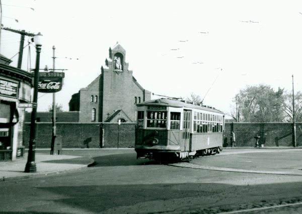 "Car number 5690 makes the turnaround at Hyde Square in April of 1949. On the left can be seen a drugstore with a ""Drink Coca-Cola"" sign. Also on the left a sign reads ""Watch Repair"". The ""Centre St."" sign can also be seen clearly on the left.   A chapel can be seen behind the brick wall.  Three school buildings operated by the House of Angel Guardians were also on the grounds. Photograph courtesy of  Frank Cheney.    For maps and further history, see these two links:    Remember Jamaica Plain?     Bill Milhomme Blog"