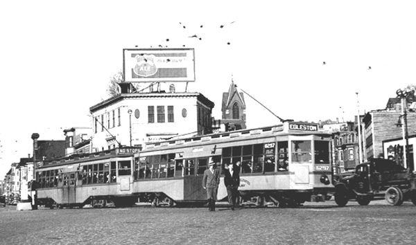 "Car 6297 carries an Egleston sign as it makes the bend in Jackson Square at Columbus and Centre Streets in March 1938. Note the ""Pickwick Ale"" billboard. The white building directly behind the trolley houses the Wm E. Mooney Club and Spencer's Lunch. These cars were the mainstay of the subway for years. They weighed half as much as a modern Light Rail Vehicle yet held the same number of passengers."