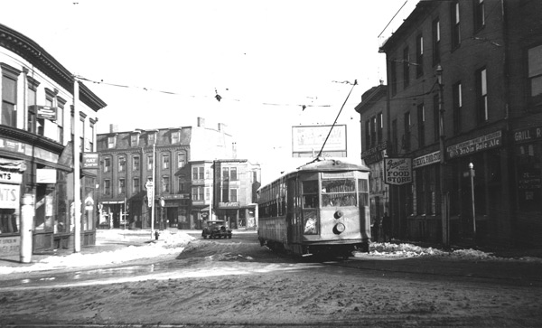"In this February 1938 view, car 5958 travels down Guild Row in Dudley Square. Although difficult to see without enlargement, signs in the square advertise ""General Self Service Food Store"", ""Roxbury Hat Shop"", ""Roxbury Employment Center"", ""Roxbury Tavern"", and ""India Pale Ale."" Other signs advertise a barber shop, auto supplies, and a key-making service."