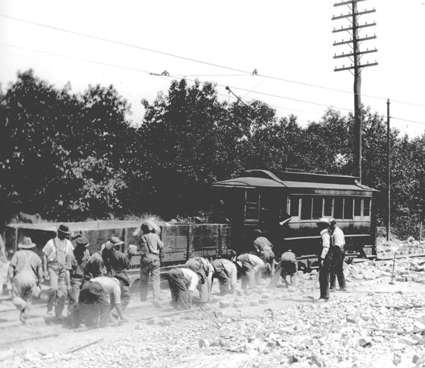 Workers removing paving stones from track bed during maintenance work in West Roxbury ca. 1897.