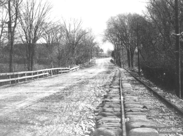 "This photograph was labeled ""South of Spring Street"" and shows sandbags on the line to Needham, probably in Dedham. The sand bags were probably placed there to protect the track bed from flooding."