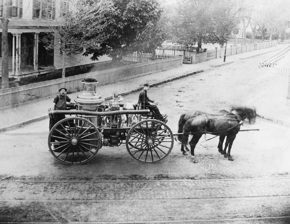 Two firemen pose with a horse-drawn chemical fire engine in this 1880 photograph taken at Centre and Burroughs Streets. These engines used chemicals rather than water to fight fires.