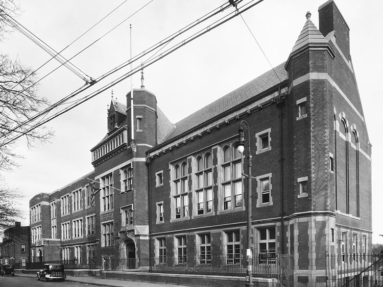 The Jamaica Plain High School at 76 Elm Street was built in 1900. The impressive building is designed in Tudor Revival style. An addition was built in 1925. The school was one of the first in the school system equipped with electric clocks manufactured by the Blodgett Clock Company. No longer used as a school, the building has been converted to residential purposes. Photograph courtesy of David Rooney.