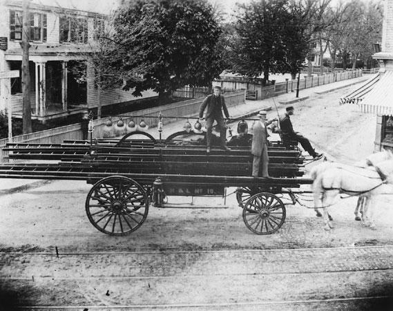 This hook and ladder wagon was photographed in 1885 at the corner of Centre and Burroughs Streets. John Lynch is the driver of Ladder 10. Mark Davis is the call captain standing at the center of the truck. The Seaverns House is visible to the left.