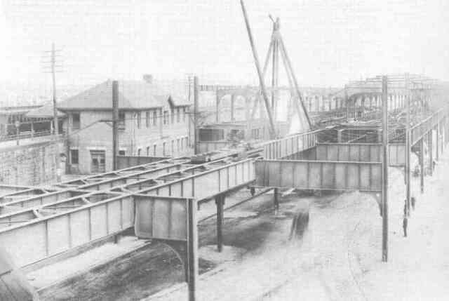 Construction work nears completion on the Forest Hills Orange Line station in 1908. The Boston & Providence Railroad station is seen on the left.