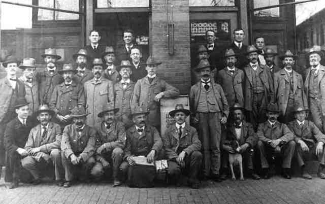 U.S. Postal Service employees pose outside the post office bulding in Woolsey Square near the current location of the Green St. Orange Line station.