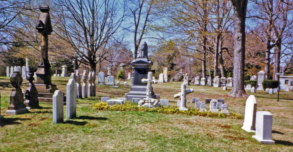 The Lowell family burial plot at Forest Hills Cemetery in Jamaica Plain. The stones for 'Old Judge' John Lowell and for his son, 'The Rebel' are on the left. The Old Judge was removed from the family tomb at the Boston Common Burial Ground in 1895 to allow for the construction of the Boylston Street subway. The author acknowledges with gratitude Ms. Dee Morris for her assistance in locating the Lowell plot.  Augustus Lowell, who sold and subdivided his family's estate, is buried with his family in another part of the cemetery. Photograph courtesy of Richard Heath, April 28, 2001