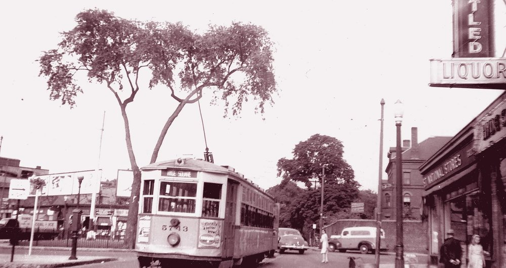 A trolley heads down Centre Street towards Jackson Square in this view of Hyde Square circa 1940.  Download photo .