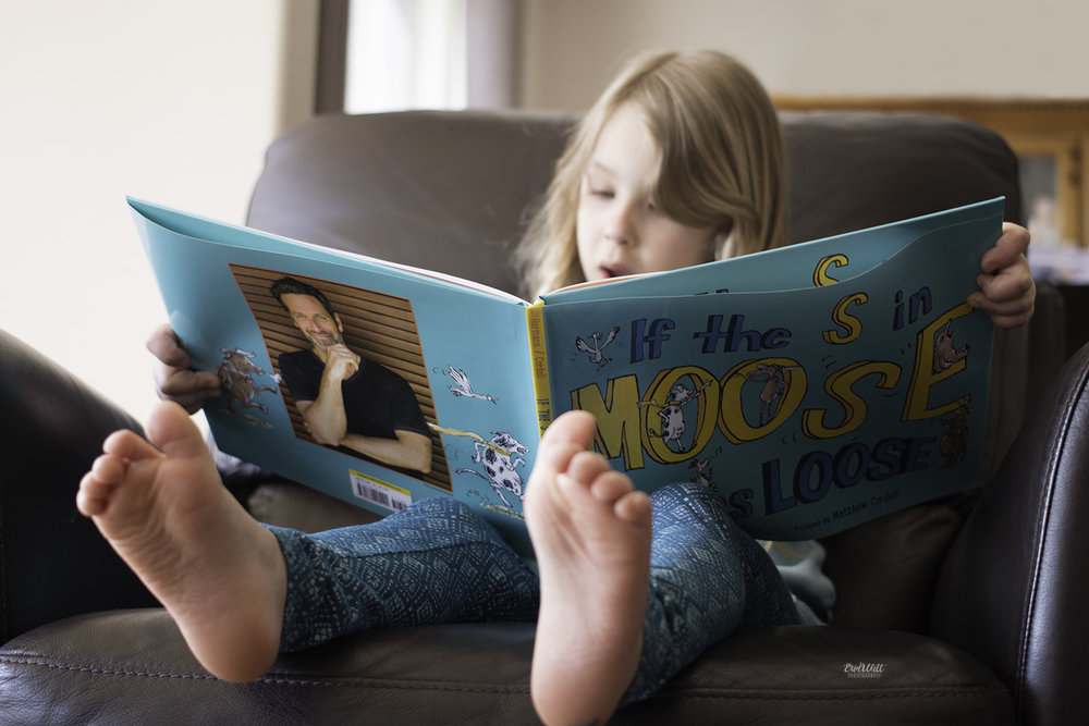 family photography Kitchener - Child reading a book called If The S In Moose Comes Loose by Peter Hermann
