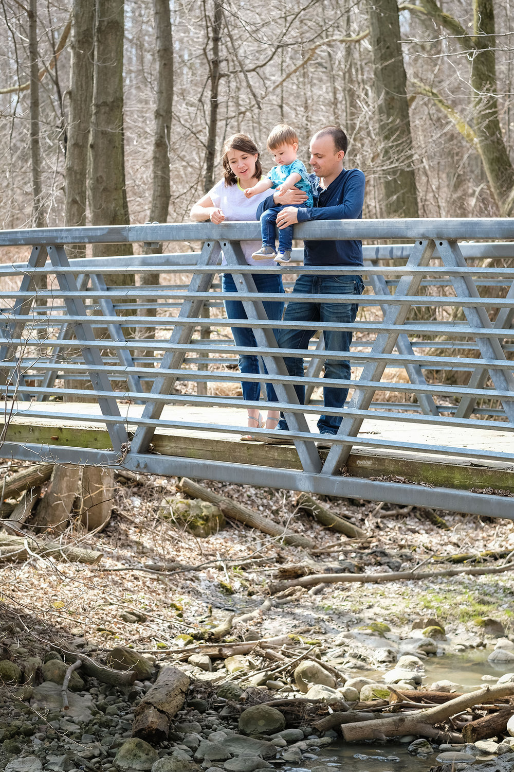 Family standing on a small bridge looking down into a stream in the forest on a sunny day Family photography Kitchener-Waterloo
