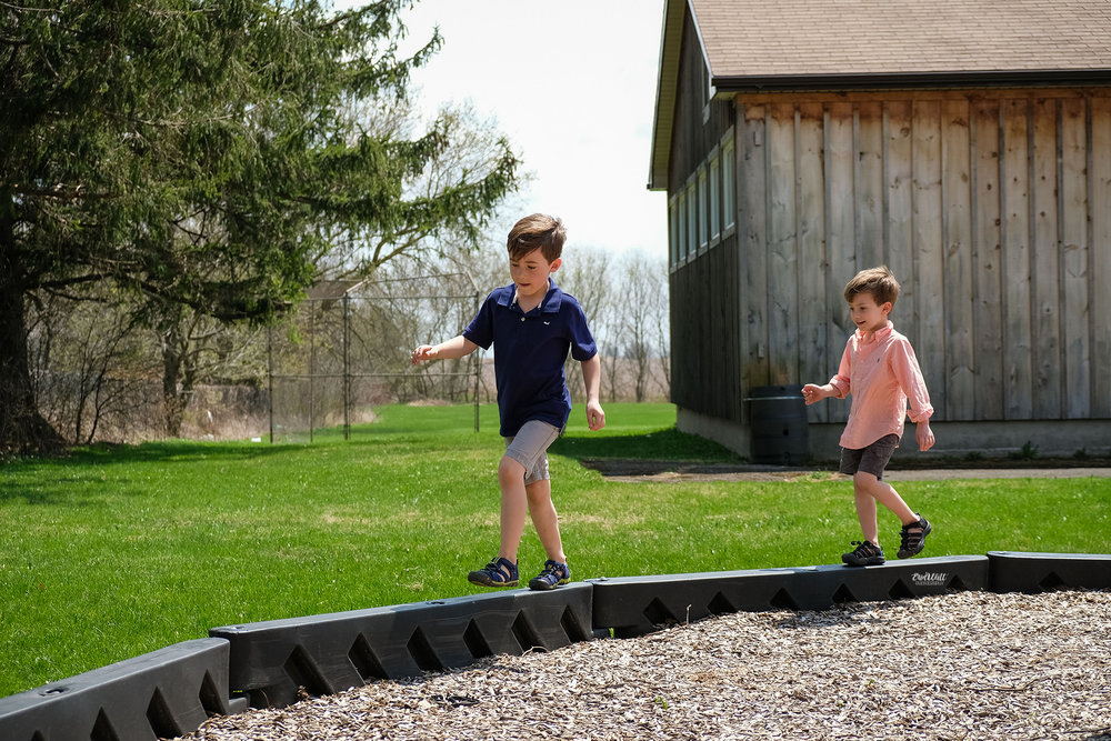 Two boys balancing on a small divider outside on a sunny day family photography Kitchener-Waterloo